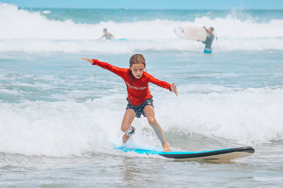 Kid Standing Up First Time Surfing Lesson Go Ride A Wave