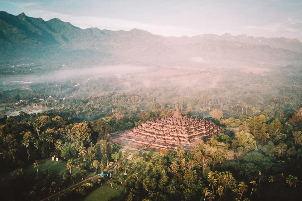 Drone shot of the Borobudur complex by sunset