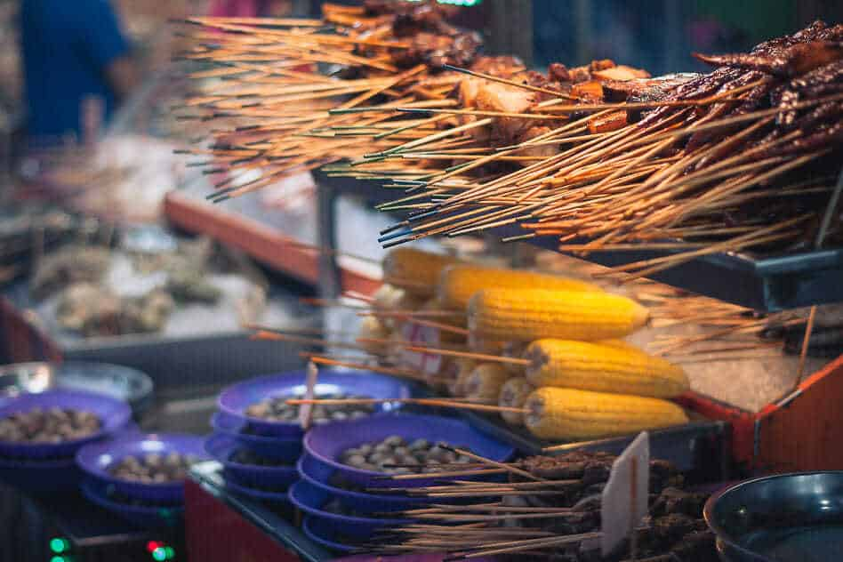 For family travel on a budget, eat local street food like this hawker in Kuala Lumpur